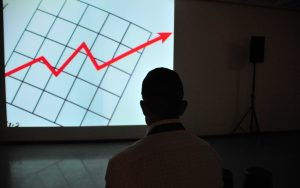 Man Looking At Effective Investment On Projector
